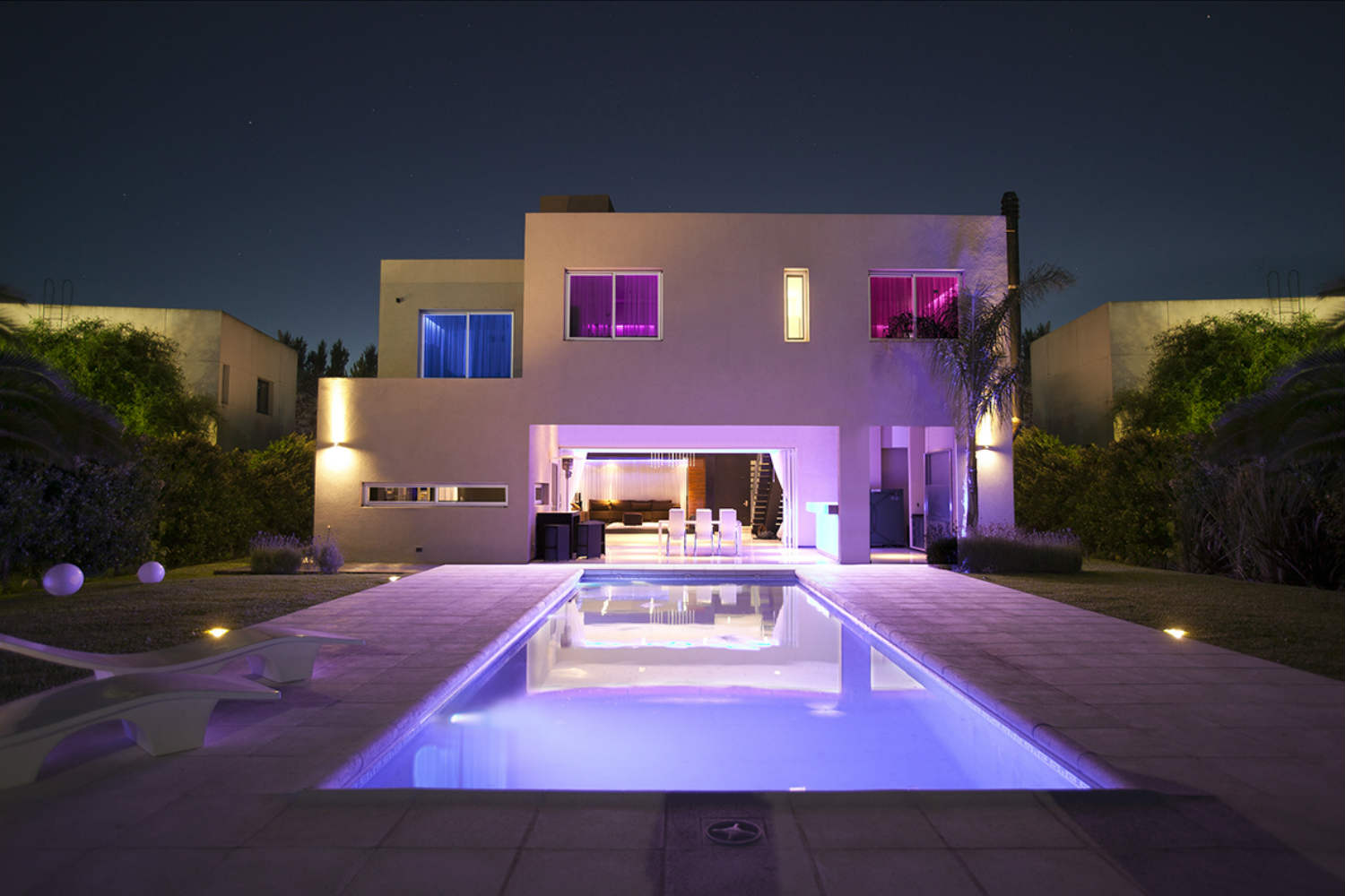 Casa Fontela in Buenos Aires, Argentina designed by WSDG. Backyard with LED illuminated swimming pool at night