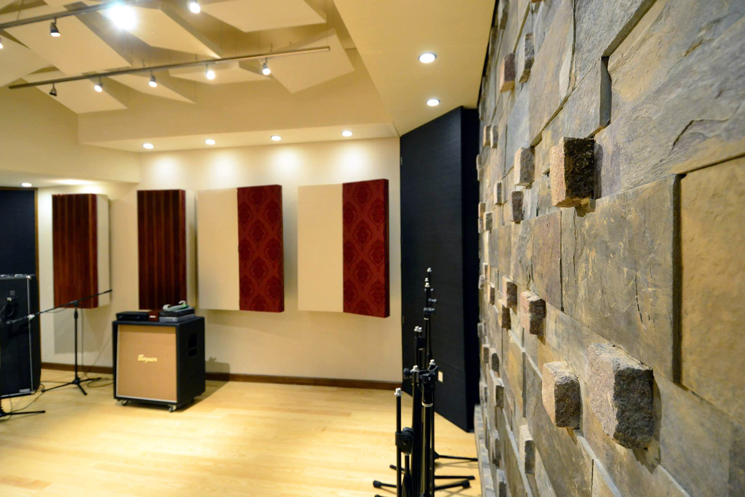 Jose Gentile home recording studio designed by WSDG in Cordoba, Argentina. Live Room wall featuring natural stone wall.